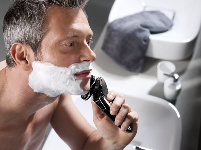man uses Philips Norelco SensoTouch 3D/1250x shaver in bathroom