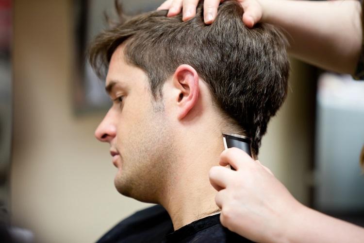 a barber cutting a man's hair with a hair clipper