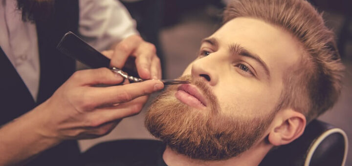 a young attractive man having his beard trimmed