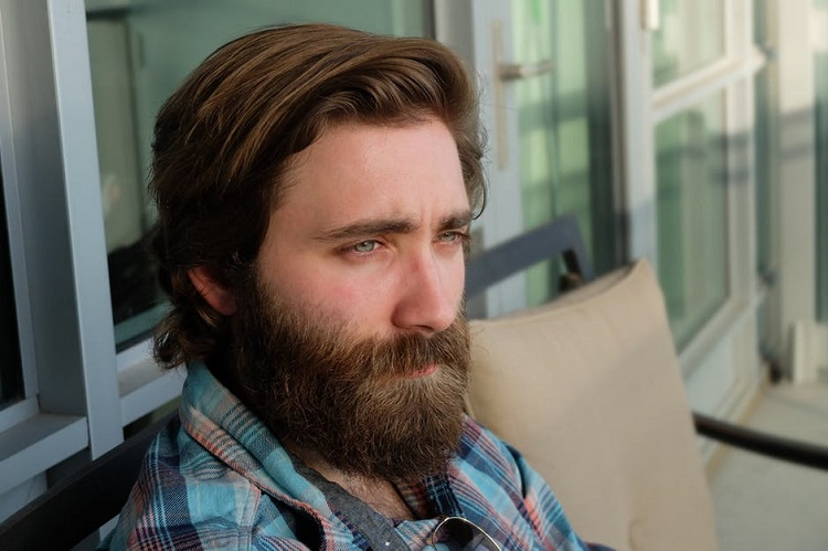a man's face with thick hair and beard
