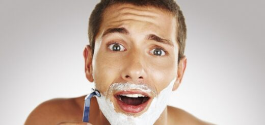 a young man looking surprised while shaving