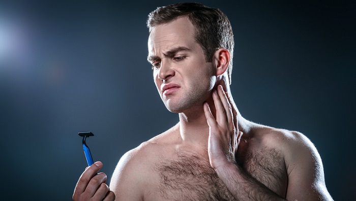 a young man with a shaving razor