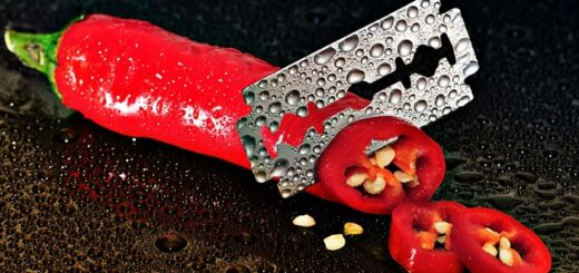 a razor blade cutting through a red pepper