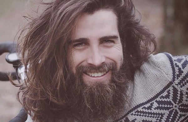 a smiling attractive man with long hair