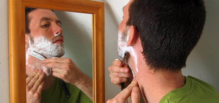 a young man shaving and looking in a mirror