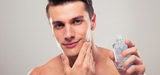 a young attractive man applying aftershave on his face and holding an aftershave bottle in his other hand