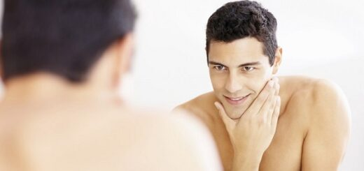 the reflection of a young man looking in the mirror with a freshly-shaved face