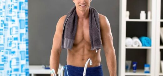 Handsome young man in bathroom towels smiling and looking at the mirror