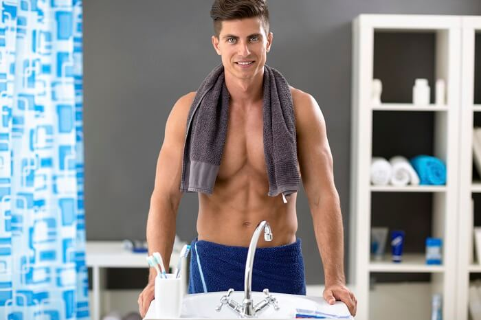 handsome young muscular man in towel in bathroom smiling in the mirror