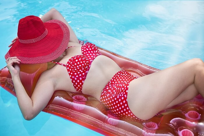 woman in red bikini with face covered by big red hat in a swimming pool