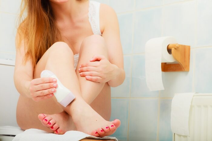 Woman shaving legs in the bathroom using electric shaver