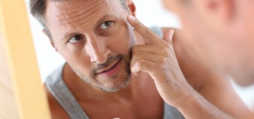 man in bathroom applying skin care product on face in the mirror