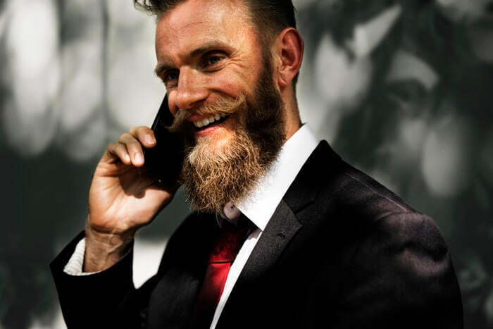 elegant business man smiling with long beard talking at the phone