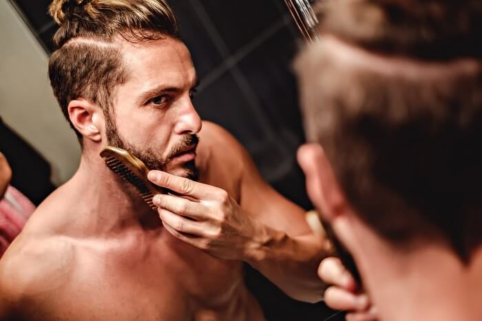 hipster man with man bun focusing on combing beard in bathroom