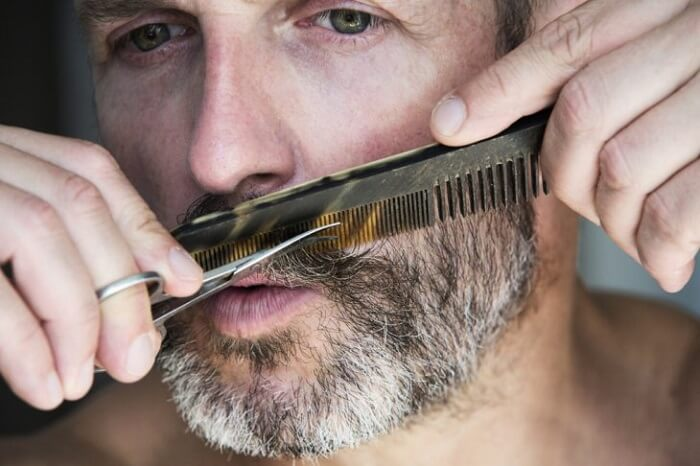 man with grey hair trims his mustache and beard with scissors and comb