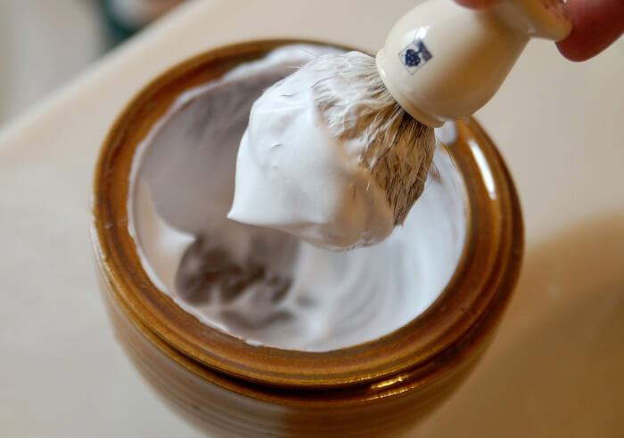 shaving lather in wooden bowl taken out with brush