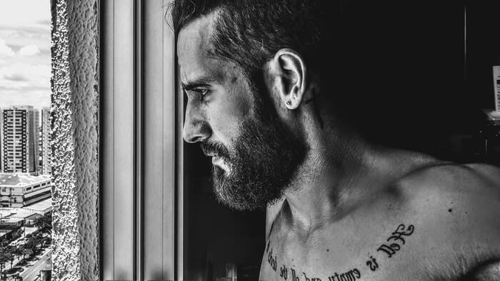 black and white of a tattooed man with beard looking through the window