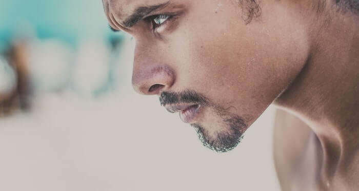 naked young man bust from profile looking down with goatee