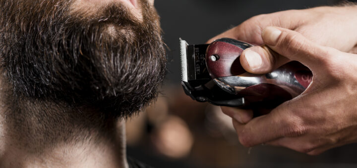Close-up of a hairdresser's hand shaving man's beard with williams lectric shave trimmer