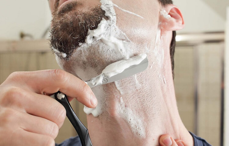 man shaving with a straight razor