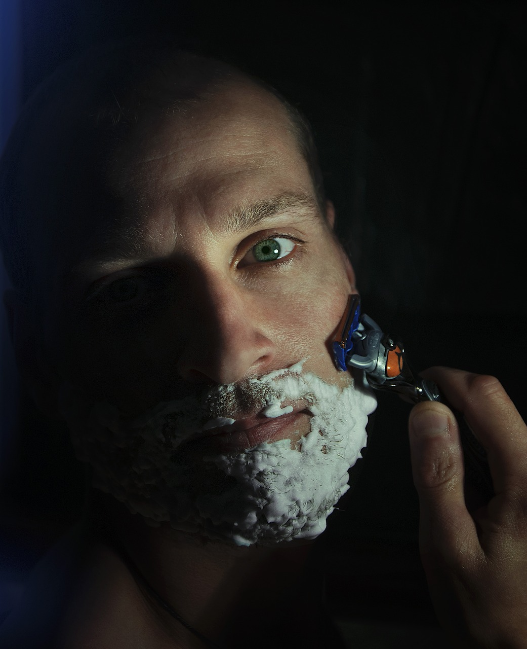 man with shaving cream and shaving his beard with a Gillette Safety Razor