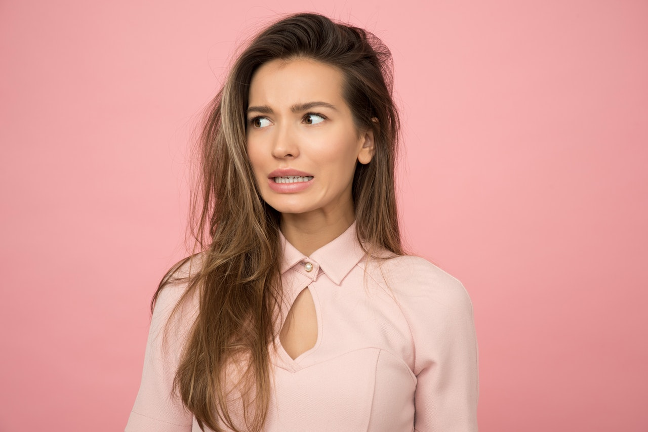 woman wearing a pink top with weird facial reaction