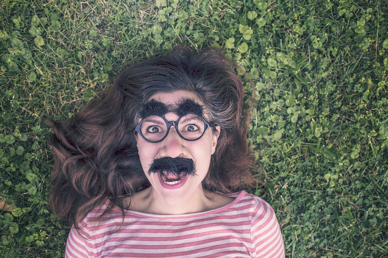 girl wearing thick eyebrows and a fake beard while lying down on the ground